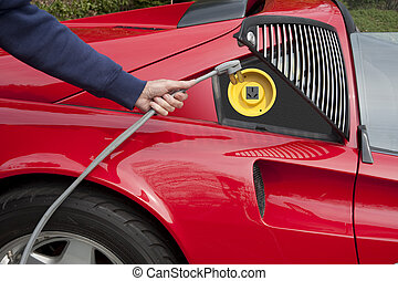 Recharging electric car - Red electric car home recharging...