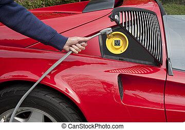 Recharging electric car - Red electric car home recharging...
