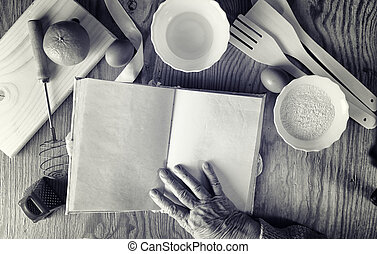 Recipe book in the hands of an elderly woman
