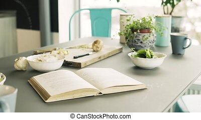 Recipe book, spinach and garlic on a table in kitchen.