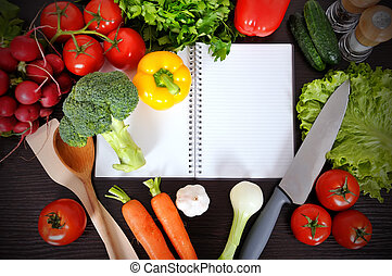 recipe book with vegetables and herbs on wooden background