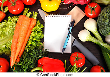 recipe book with vegetables on kitchen table