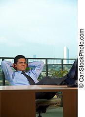Reclined Hispanic Businessman Hand Behind Head