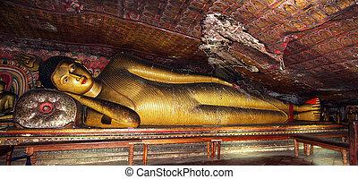 A reclining golden Buddha in the painted Dambulla Rock caves, Sri Lanka