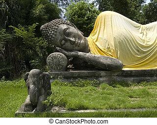 Reclining Buddha in lush, green garden. Muang Boran, Samut Prakan, Thailand.