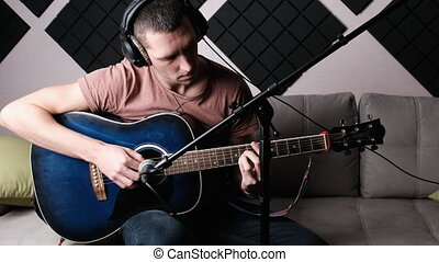 Recording an acoustic guitar in a home recording studio. A young man sitting on a sofa in headphones plays the guitar in stylish room made of acoustic foam rubber. Blogger learning to play the guitar.