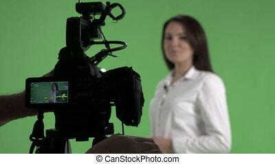 Recording in virtual green chroma key studio woman talking to camera