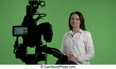 Recording interview in virtual green chroma key studio woman...