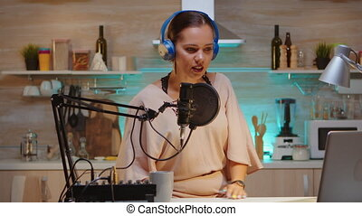 Influencer wearing headphones recording new podcast series for her audience. On-air online production internet broadcast show host streaming live content, recording digital social media communication