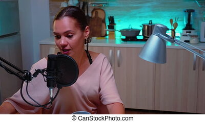 Woman vlogger recording podcast in home studio iluminated with neon light. Creative online show On-air production internet broadcast host streaming live content, recording digital social media communication