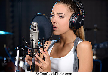 Recording Studio - Portrait of young woman recording a song...
