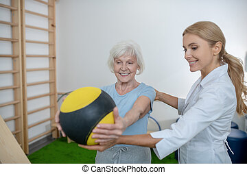 Grey-haired woman exercising with a ball in a rehabilitation center
