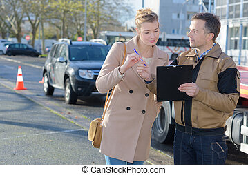 Recovery man asking customer to sign paperwork