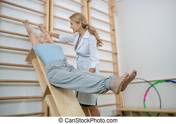 Old patient exercising in a rehabilitation center with instructor