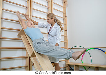 Old woman exercising in a rehabilitation center with instructor