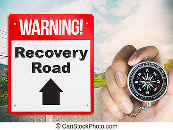 Recovery Road concept sign with holding compass for direction