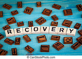 recovery word written on wood block. Wooden alphabet on a blue background