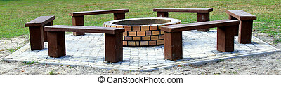 Recreation area in forest with fire-pit and bench