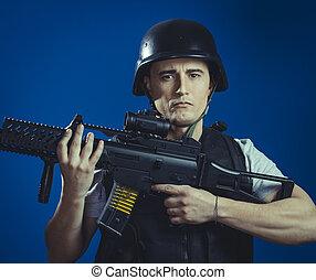 Recreation, paintball sport player wearing protective helmet aiming pistol ,black armor and machine gun