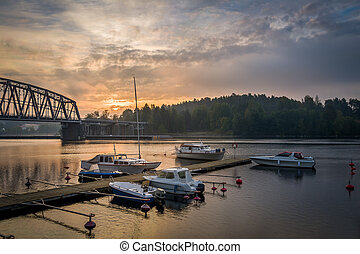 Recreational boats at sunrise. Lake pier and romantic mood ...