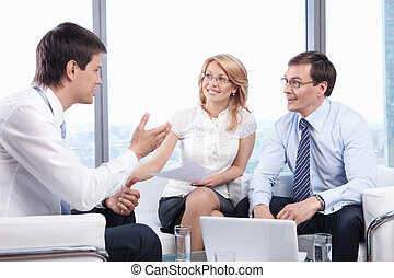 Recruitment - Two people listen to a young man in the office