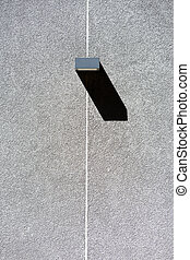Rectangular lantern with a shadow on a gray wall