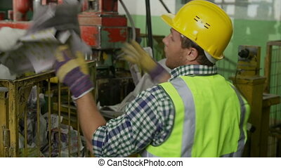 Recycle Tankhouse - Workers restacking waste from truck into...