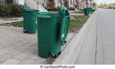 Green recycling bins sit on the curb in a suburban area. Toronto, Ontario, Canada.