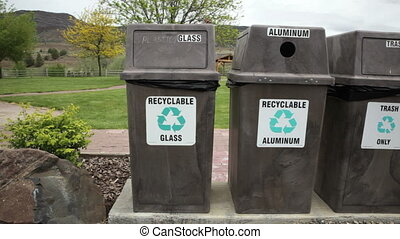 Recycling Bins - Three recycling bins and trash cans in a...
