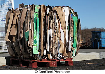 Segregated flattened and stacked waste cardboard and packaging stands on a pallet ready for recycling to save the environment.