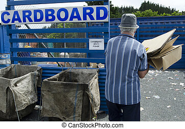 Recycling Center - Man throwing cardboard waste in recycling...