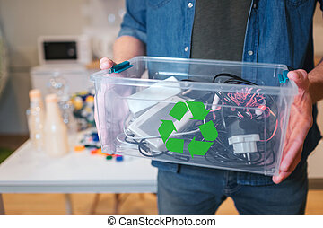 Recycling concept. An electronic waste in recycling contaner close-up. Responsible man is protecting environment while sorting the waste at home