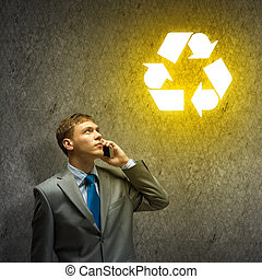 Young thoughtful businessman looking up a recycling symbol