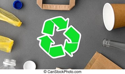 green recycle symbol with household waste on grey - ...