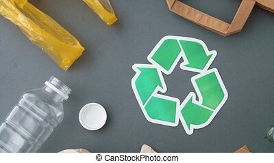 green recycle symbol with household waste on grey -...