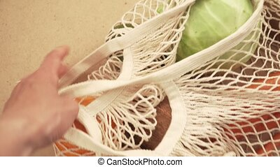 Recycling mesh string bag full of vegetables and fruits, eco...