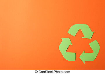 Recycling sign on orange background, top view