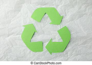 Recycling sign on white crumpled paper background, top view