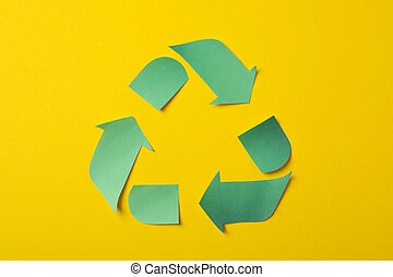 Recycling sign on yellow background, top view