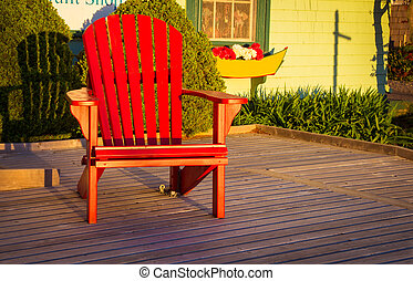 red Adirondack chair in morning light on a deck