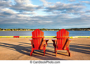 Red adirondack chairs - Two red adirondack chairs on the...
