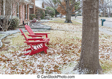 Red adirondack chairs with snow covered at front porch entrance of suburban house in Texas, USA