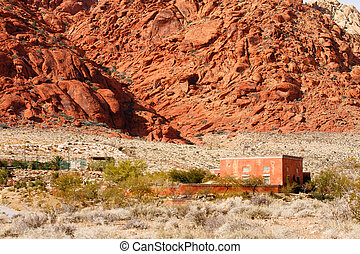 Red Adobe Home in Desert by Mountains