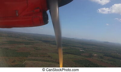 red aircraft flies above plantations and tropical jungle