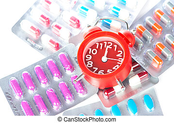 Red alarm clock and medical blister pack