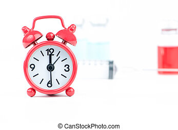 Red alarm clock and medicine background