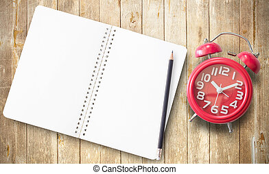 Red alarm clock and note book on brown wooden