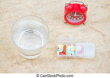 Red alarm clock, daily pill box and glass of water show medicine time