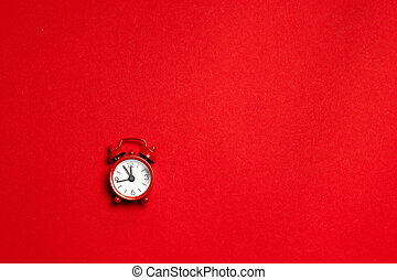 Red alarm clock in a minimal style on a red background. Flat lay. Holiday concept