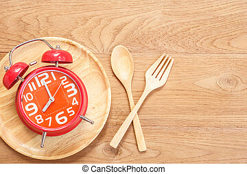 Red alarm clock in wooden dish, spoon and fork on wooden ...